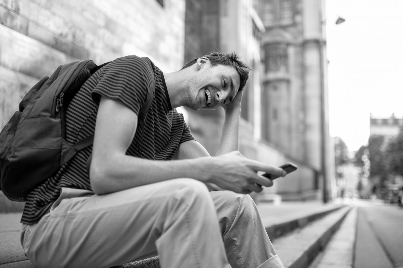 Side portrait of happy young man sitting outside in city with cellphone and bag